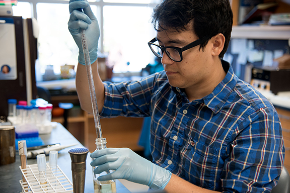 male grad student working in a lab with test tube